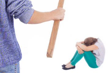 Boy holding a wooden stick to beaten on a little girl, isolated