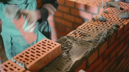 Worker build brick wall with trowel at construction site