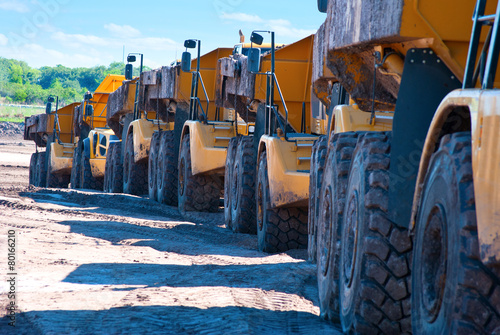 Row of dump trucks driving through construction zone - 80166210