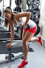 Young female at the gym working on her triceps and back