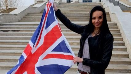 Brunette women with UK Union Jack flag posing smiling outdoors