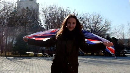 Teen girl with Union Jack waving by the wind and smiling