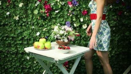 Beautiful woman puts bunch of flowers on table next to hedge
