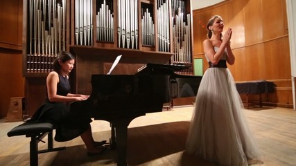 Review woman pianist playing piano and beautiful opera singer