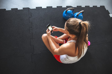 Young woman with smartphone at the gym,workout break