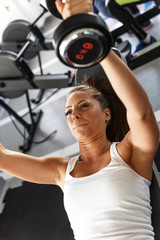 Woman lifting  weights and working on her biceps at the  gym