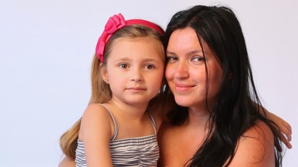 mother brunette embraces daughter and smile close up