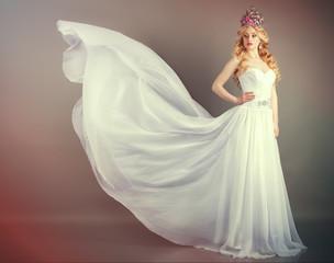 Bride in flying wedding dress in the studio