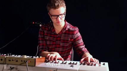 Young man in glasses plays synthesizer in dark studio