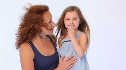 mother embraces daughter and they speak while in them blows wind