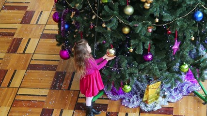 Little girl touch the ball at Christmas tree with colorful toys