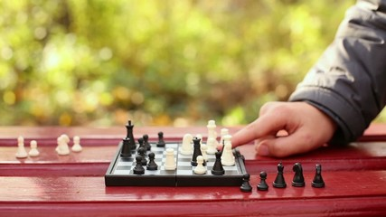 Grandmother and child hands move chessmen on chessboard