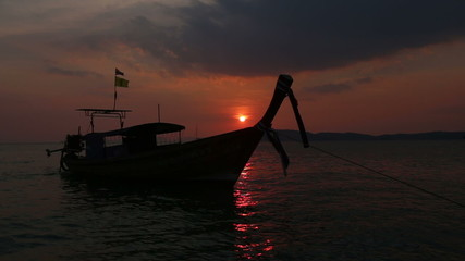 silhouette of thailand motor longtail boat rolls on waves sunset