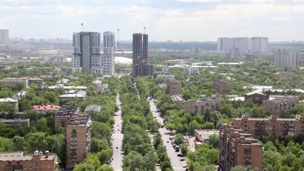 city landscape with boulevards, multi-storey buildings and green plantings between