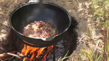 Broiled onion with meat boils in hot oil at pot on campfire