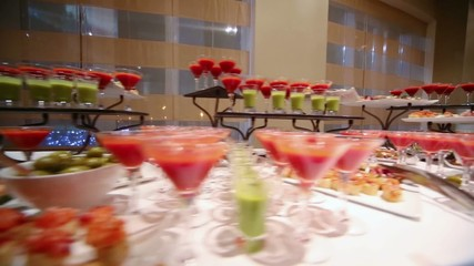 Restaurant table covered with colored cocktails and sweet snacks