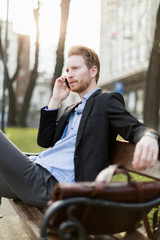 Businessman sitting on a  bench  and talking on the phone