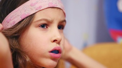 Little girl with trainer for straightening teeth wears headband