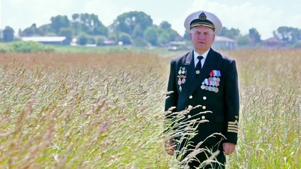Old man in marine uniform stands among grass in field