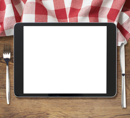 black tablet pc on wooden table with fork and knife