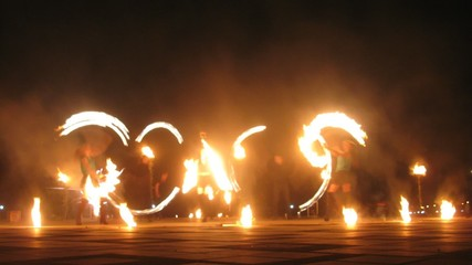 Group of man and women performing a show with flames, timelapse