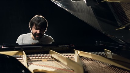 Pianist emotionally sings and plays the piano in a dark room