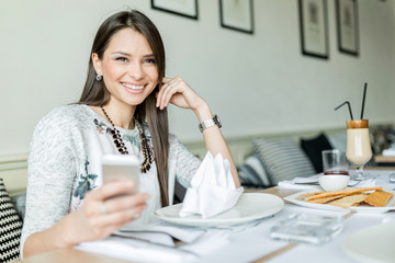 Beautiful smiling lady sitting in a restaurant and holding her p