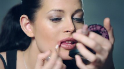 brunette girl does lips makeup with mirror at photo studio