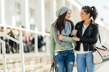 Two young girls walking the streets and shopping happily