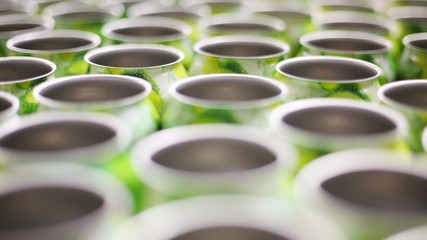 Many empty aluminum cans for drinks move on conveyor, close-up
