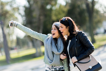 Two young and beautiful women taking a selfie of themselves