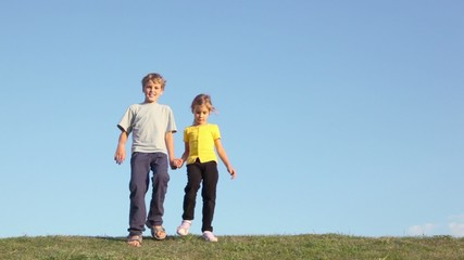 Two kids boy with little girl hold hands and approach from behind of grass hill at sunny summer day