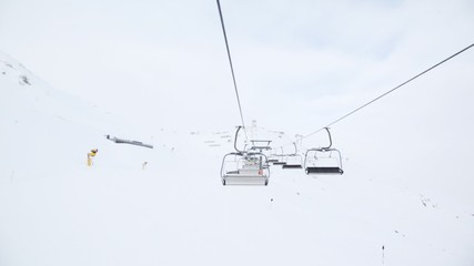 Cabins of chairlift move up and down over hillside