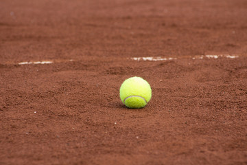 One green tennis ball on the clay court