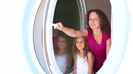 mother and her little daughter look out from round window