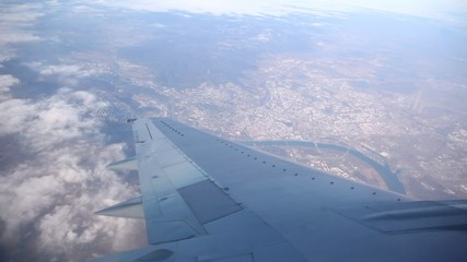 Wing and the city are visible from a plane window.