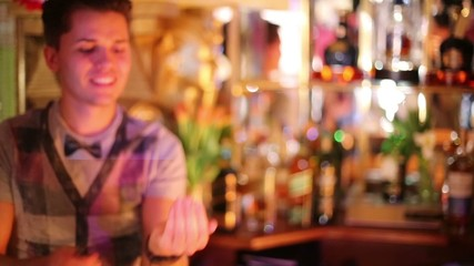 Young bartender ignites mixture on palm and blows it in bar