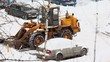Bulldozer removes snow near car at parking in winter day