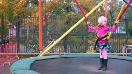 Little girl stands on trampoline with rope support and people walk in park