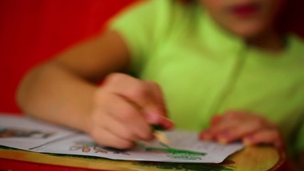 Little girl draws on paper by green pencil, closeup