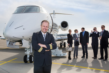 Pilot standing in front of corporate private jet