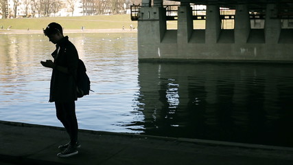 Student texting on smartphone and walking under the bridge