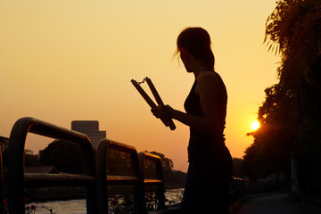 women and nunchaku in hands silhouette in sunset, martial arts