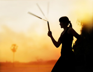 martial arts, women and nunchaku in hands silhouette in sunset