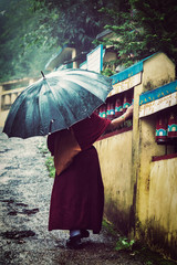 Buddhist monk with umbrella spinning prayer wheels