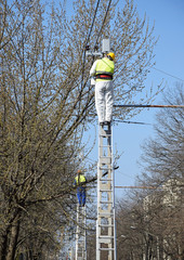 Two electrician are working on the pylon