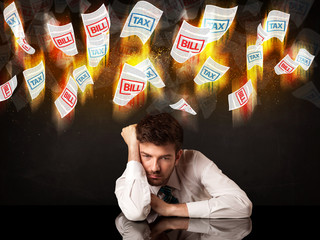 Depressed businessman sitting under burning tax and bill papers