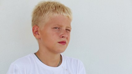 Young boy with blond hair stay close up near the wall