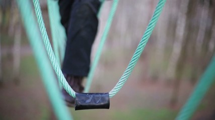 Steps of boy and green swinging ropes at autumn day.