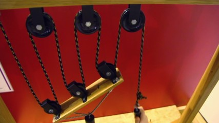 Hand pulls rope with pulleys and cylinder on wooden plate